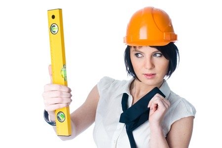 Young female worker with protection helmet and level at isolated background Stock Photo