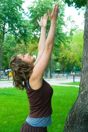 save tree: Young woman relaxing in city park