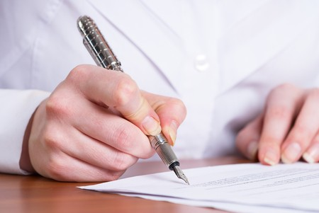 persons hand signing an important document