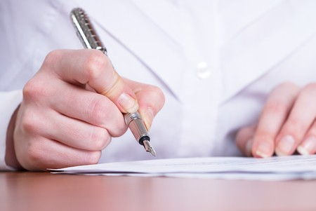 Young businesswoman writing document in office photo