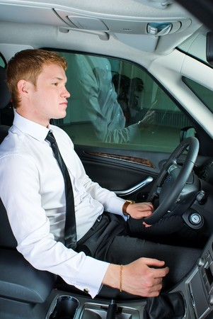 Young man driving a car in a relaxed position photo