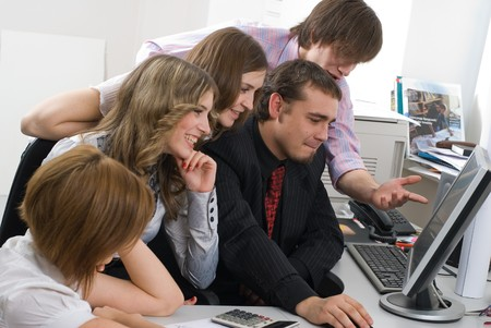 Successful business team working over a laptop computer and looking et documents photo