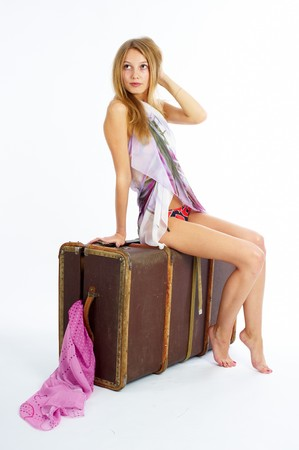 Young beautiful blonde with suitcase at white background photo