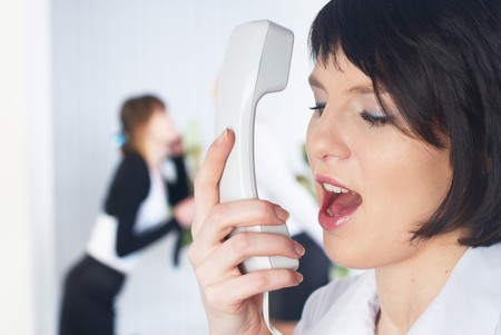 Young businesswoman calling by phone in office photo