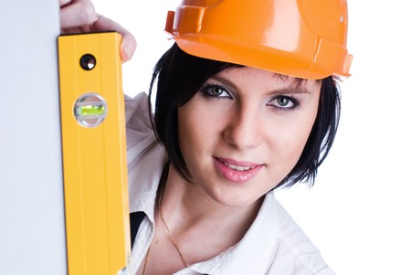 Young female worker with protection helmet and level at isolated background photo