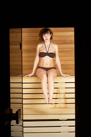 Young woman sitting on wooden bench in sauna cabin photo