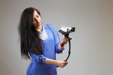 Young happy woman holding small video camera.at white background photo