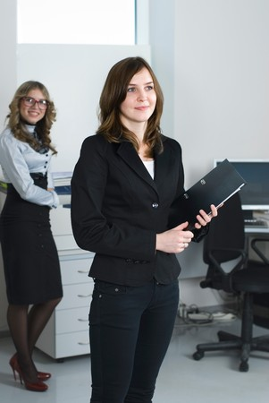 Smiling business woman in office at her collegues background photo