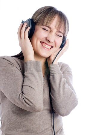 Young woman with headphones listening to loud music at isolated background. photo
