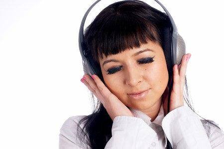 Young woman with headphones listening to loud music at isolated background. Stock Photo - 8109622