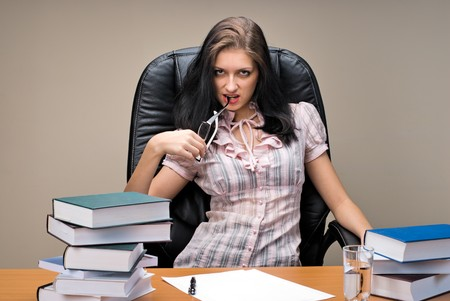 Young woman-boss sitting behind table in office photo