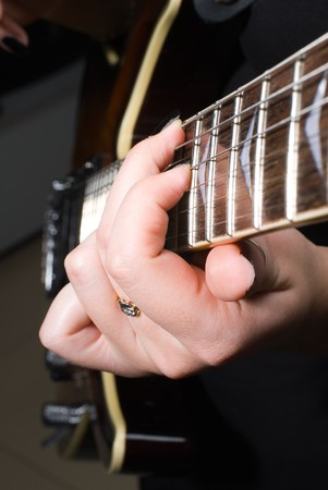 Woman hands playing on guitar, Closeup view photo