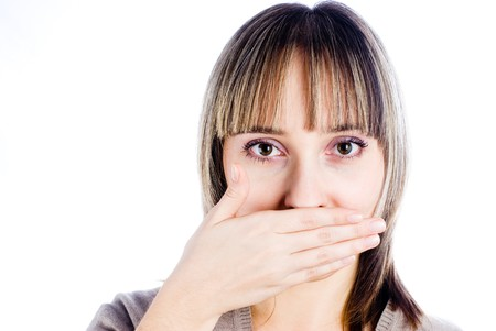 mouth closed: Joven rubia cubriendo su boca con la mano  Foto de archivo
