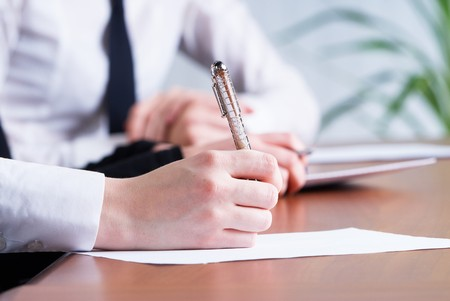 Young business woman writing document in office photo