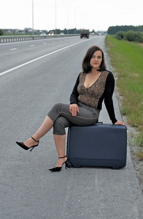 Travelling woman with suitcase waiting on road photo