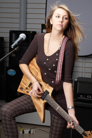 Young woman with rock guitar at music equipment background photo