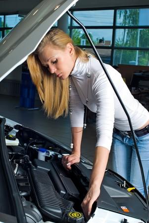 Young woman at broken car photo