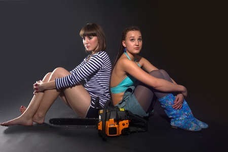 Two pretty girls with chainsaw photo