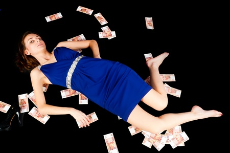 Young beautiful woman laying among currency, isolated on black photo
