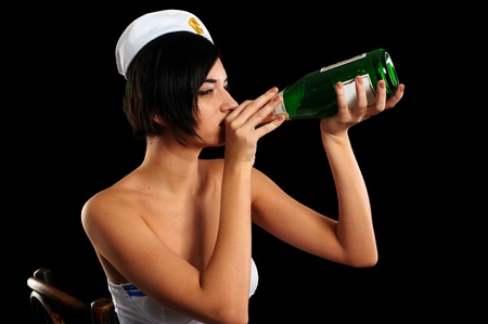 dark haired woman: Young beautiful woman in sailor costume with wine bottle  Isolated on black