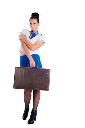 Attractive young stewardess with old suitcase, isolated over white background photo