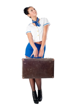 Attractive young stewardess with old-fashioned suitcase  Isolated on white photo