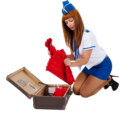 Attractive young stewardess packs clothes in old-fashioned suitcase photo