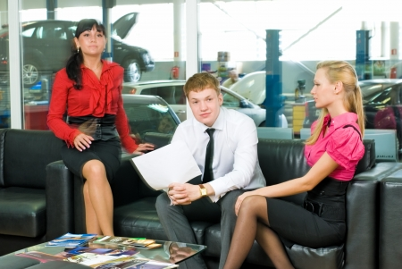 Young family in car sale office talking with manager photo
