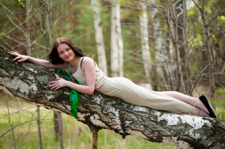 dark haired woman: young pretty woman laying on birch in forest Stock Photo