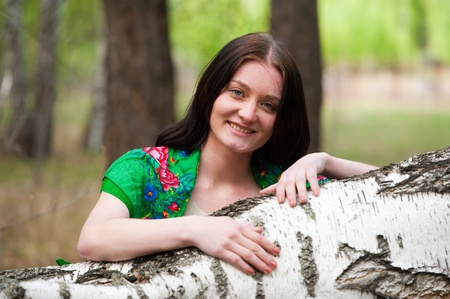 young pretty woman standing near birch in forest photo