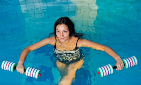 water aerobics: Young woman aquaaerobic training in fitness center pool