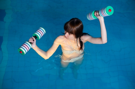 Young woman aquaaerobic training in fitness center pool photo