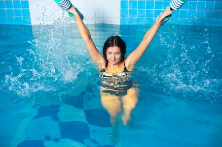 Young beautiful woman doing aqua gym exercise with water dumbbell in a swimming pool photo