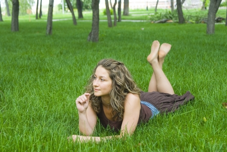 portrait of beautiful young woman lying in park  photo