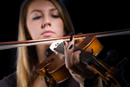 Young woman playing on violin on dark background photo