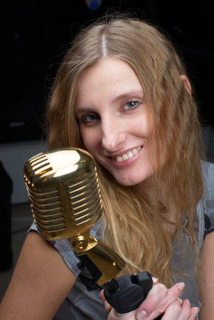 Female singer with vintage microphone at black background photo