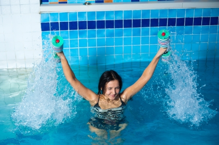 Young woman aquaaerobic training in fitness center pool