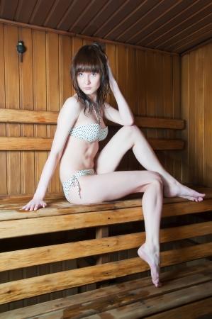 finland�s: Mujer hermosa joven que se relaja en una sauna caliente