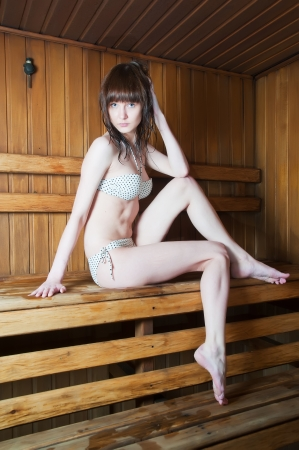 steam room: Young beautiful woman relaxing in a hot sauna