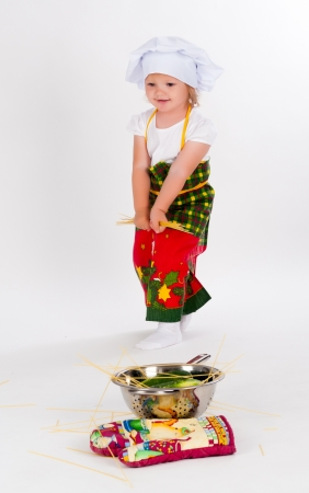 Cute little cook girl with noodles on a white background photo