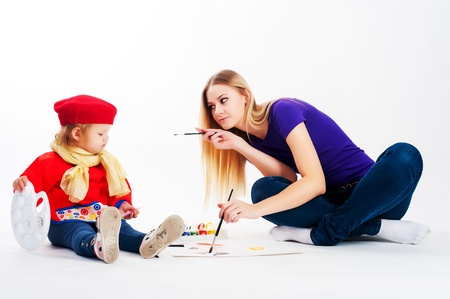 Beautiful young woman with daughter drawing by paintbrush photo
