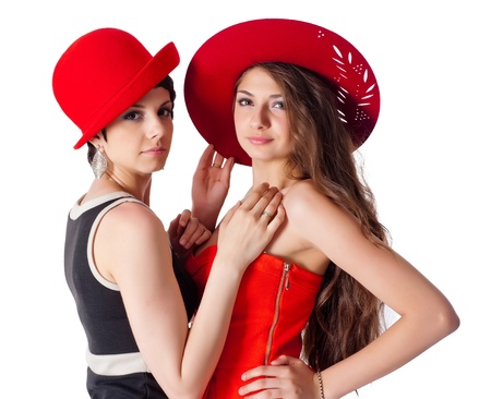 Two attractive young women with hats  Isolated on white photo