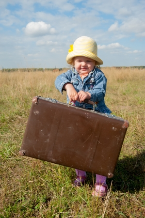 Young beautiful girl with suitcase at country side photo