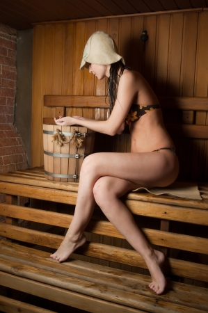 Young beautiful woman relaxing in a hot sauna photo