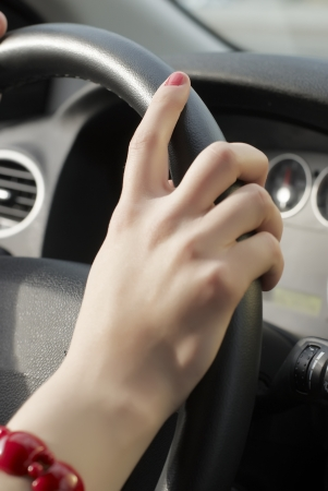 Girl hand on wheel steering on driving photo