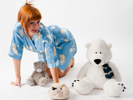 Charming red girl wearing pajamas embraces teddy bear on white background Stock Photo - 17244346