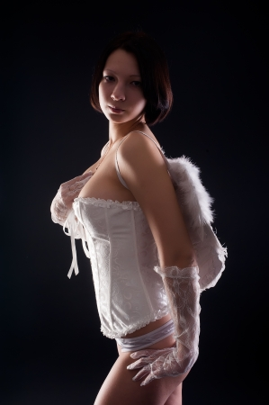 young woman with white wings like an angel at black background photo