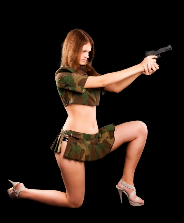 Sexy young woman with a gun isolated on black photo