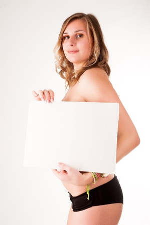 young sexy woman standing hold blank board, cover her breast, attractive   girl hide empty card board with copy space over white background, studio shoot photo