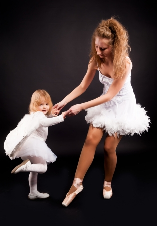 Young attractive ballerina with 2 years old angel at black background photo